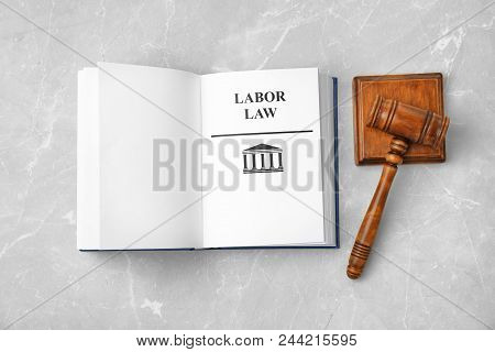 Open book with words LABOR LAW and gavel on light background, top view poster