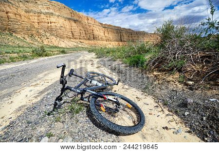 Black Mountain Bike At Country Road In The Desert Canyon. Extreme Sport Concept.