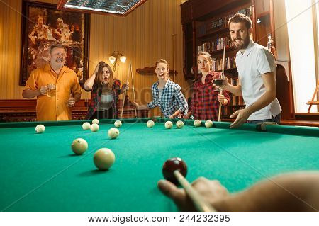 Young Smiling Men And Women Playing Billiards At Office Or Home After Work. Business Colleagues Invo