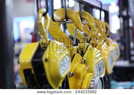 Industrial Steel Chains In Yellow Hoists ; Selective Focus