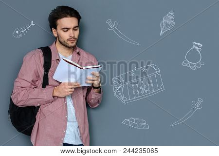 Pirate Story. Attentive Handsome Man Standing With A Backpack And Looking Concentrated While Reading