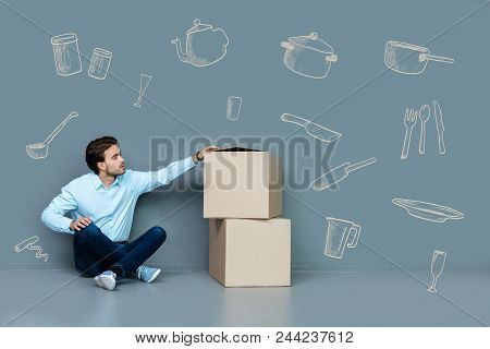 New Flat. Calm Attentive Man Sitting On The Floor And Looking Attentively At The Carton Boxes Next T