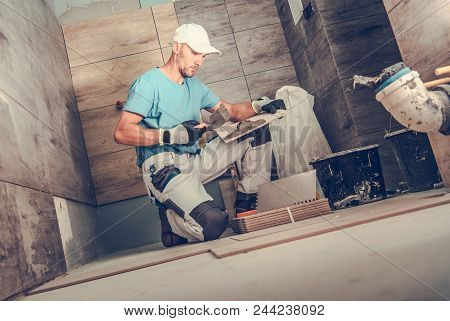 Bathroom Remodeling By Men. Caucasian Ceramic Tiles Installer During His Working Hours. Wooden Like