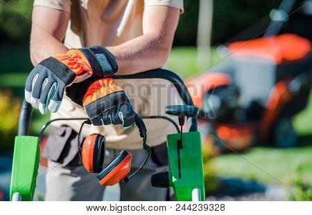 Landscaping Contractor Work. Caucasian Gardener With His Equipment.