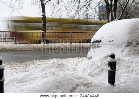 Tram Rushing By Through Snow Covered Street And Car.