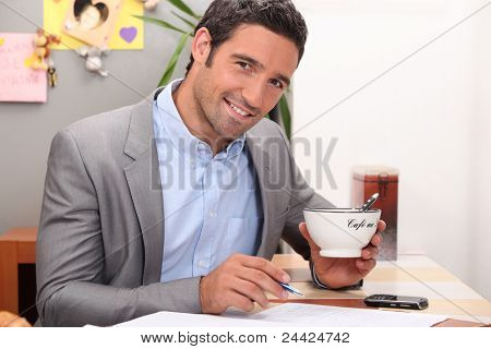 Businessman working in his kitchen with a cup of coffee poster