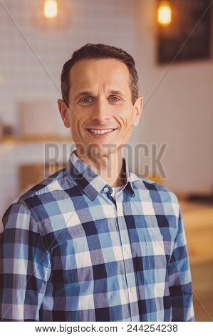 Pleased Customer. Pleasant Upbeat Young Man In A Checked Shirt Posing For The Camera And Smiling Whi