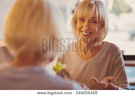 Great News. Upbeat Senior Woman Telling Her Friend Good News And Smiling At Her Brightly While Havin
