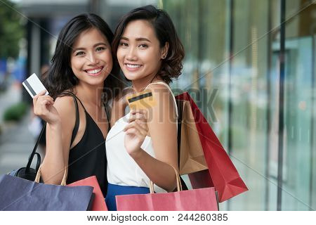 Two Beautiful Vietnamese Women With Credit Cards And Shopping Bags