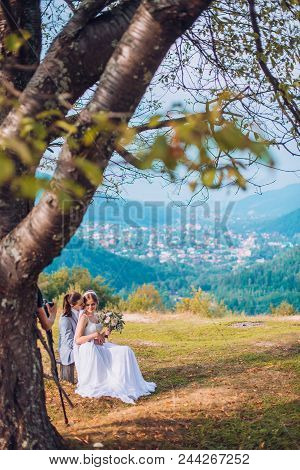 Young Couple Sitting Under The Tree In Nature. The Mountain Top Under The Tree. Wedding Day Of Bride