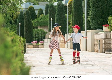 Portrait Of A Charming Teenage Couple Skating Together On Roller Skates At Park. Teen Caucasian Boy