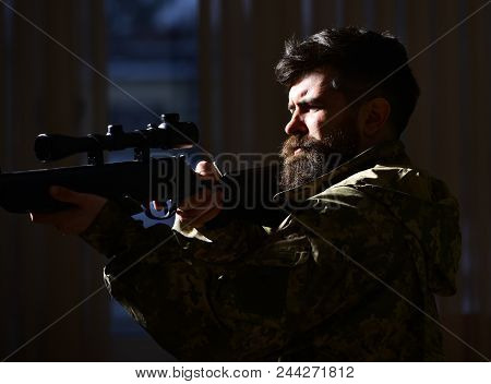 Man With Beard Wears Camouflage Clothing, Dark Interior Background. Macho On Suffering Grimace Face