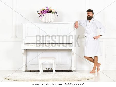 Man With Beard In Bathrobe Enjoys Morning While Standing Near Piano. Talented Musician Concept. Man