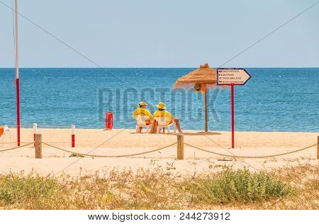 Lifeguard Dressed In Yellow Sitting On A Chair On The Beach