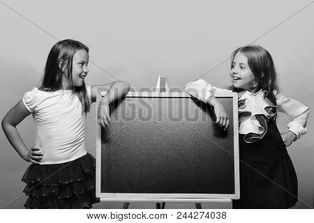 Back To School. Kids Wearing School Clothes Lean On Shiny Blackboard, Copy Space. Girls With Smiling