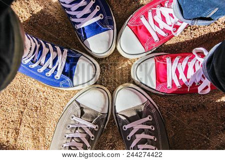Red, Blue And Gray Sneakers Standing In The Circle On Dry Sand, View From Above. Friendship, Fashion