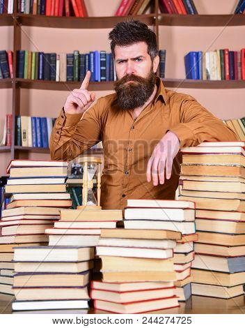Teacher Or Student With Beard Stands At Table With Books, Defocused. Librarian Concept. Man On Confi