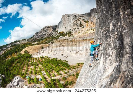 Rock Climber On A Rock. Girl In Helmet Climbs The Rock On The Background Of A Beautiful Mountain Lan