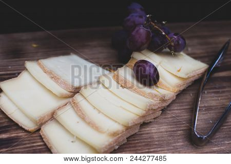 Artisan Cheese and grapes Simplicity, fresh cheese platter with red grapes still life conceptual wine and cheese party and entertaining healthy snack or rustic kitchen background photography of sliced cheese with grapes poster