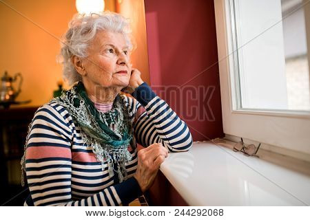 Sad Alone Senior Woman Looking Through Window At Home