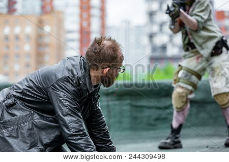 Woman Soldier, Spy Agent, Killer Or Police, Woman With A Gun In Her Hand Holding At Gunpoint A Man L