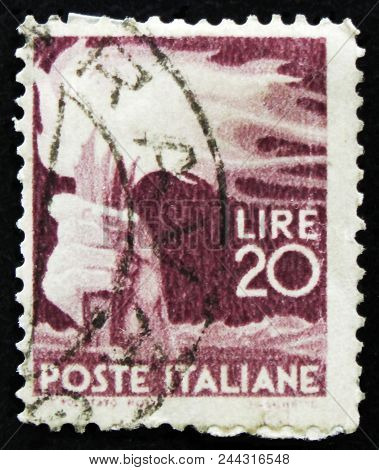 Moscow, Russia - April 2, 2017: A Post Stamp Printed In Italy Shows Hand With Torch, Circa 1945