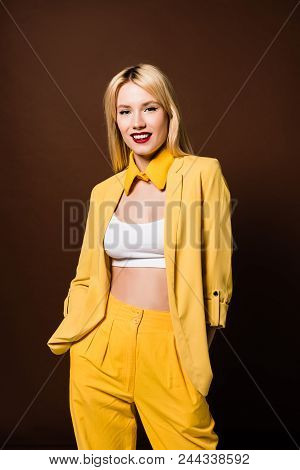 Beautiful Young Woman In Stylish Yellow Clothes Standing With Hands In Pockets And Smiling At Camera