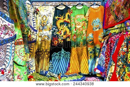 Colorful Chinese Dragon Replica Silk Garments Robes Panjuan Flea Market  Decorations Beijing China.  Panjuan Flea Curio market has many fakes, replicas and copies of older Chinese products, many ancient. poster