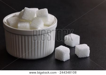 Purified Sugar Cubes On White Bowl In Side View With Copy Space. White Sugar Cubes On Black Granite