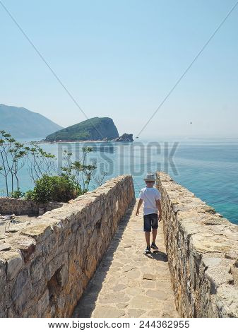 Loneliness Concept. Little Boy In A Hat Walking Away Alone To The Sea. Single Child On Empty Road.