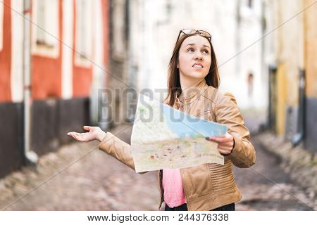 Woman Lost In The City. Confused Traveler Holding Map And Spreading Hands In Old Town. Disappointed