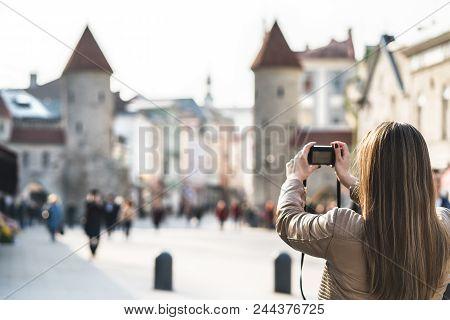 Tourist In Tallinn Taking Photo Of Viru Gate. Woman On Vacation Taking Picture Of Landmark In Estoni