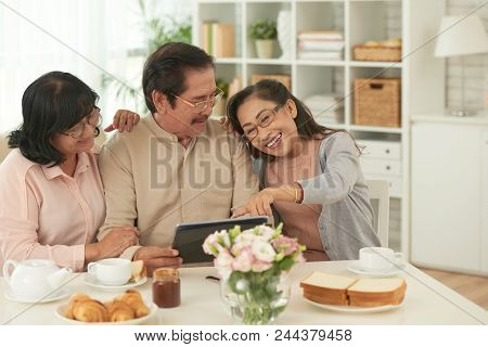 Three Friends Remember Their Happy Moments On Touchpad At The Table At Home