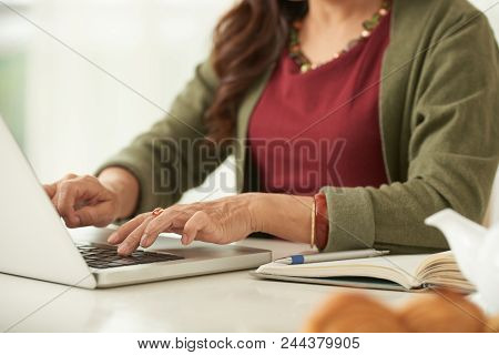 Close-up Of Senior Woman Working On Laptop At The Table