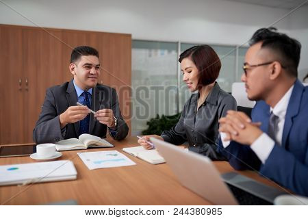 Handsome Middle-aged Entrepreneur Sitting At Wooden Table Of Boardroom And Conducting Negotiations W