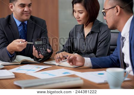Group Of Financial Managers Calculating Profits Of Their Company While Having Working Meeting At Mod
