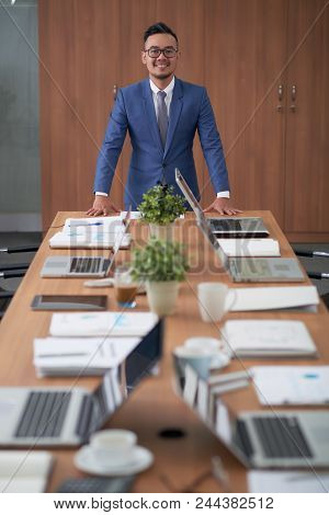 Waist-up Portrait Of Confident Asian Entrepreneur Wearing Elegant Suit Leaning On Wooden Table And P