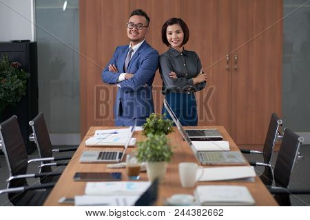 Group Portrait Of Pretty Asian Manager And Her Bearded Colleague Standing At Spacious Boardroom With