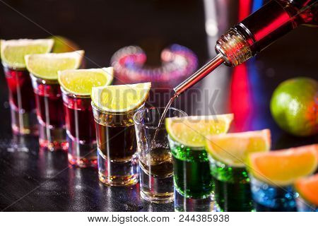 Bartender Pouring Alcoholic Drink Into Small Glasses On Bar. Colorful Cocktails At The Bar.