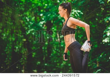 Athlete Woman Preparing For Running In Nature. Legs Warming And Stretching.