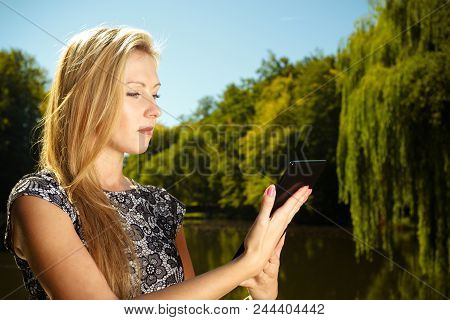 Technology, outdoor relaxation concept. Woman in park, relaxing and using tablet, ebook spending her leisure time outside poster