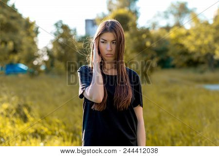 A Brunette Girl In The Fresh Air In A Black T-shirt. He Presses His Hand With His Temple. Emotions O