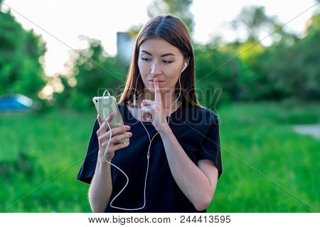 Girl In Summer In A Park In Nature. With A Gesture Of The Hand They Show It Quietly. She Pressed Her
