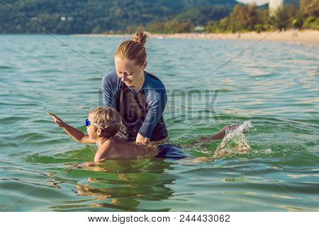 Woman Swimming Instructor For Children Is Teaching A Happy Boy To Swim In The Sea.