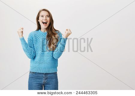 Studio Portrait Of Excited European Girl Overwhelmed With Emotions, Raising Fists In Victory, Shouti