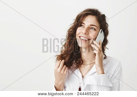 Indoor Portrait Of Positive Upbeat Caucasian Girlfriend Talking On Smartphone While Touching Hair An