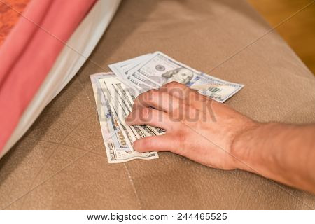 Hands With Money Hide Them Under Mattress. A Man's Hand Takes Money From Under The Pillow. A Man Hid