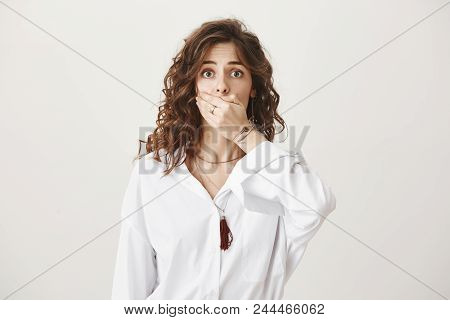 Portrait Of Sad Displeased European Female Expressing Shock And Negative Impression While Covering M