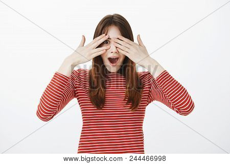Portrait Of Amazing European Girl In Casual Clothes, Covering Eyes And Peeking Through Fingers Being