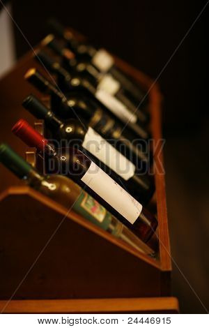 Wine Bottles Stacked On Wooden Racks Shot With Limited Depth Of Field